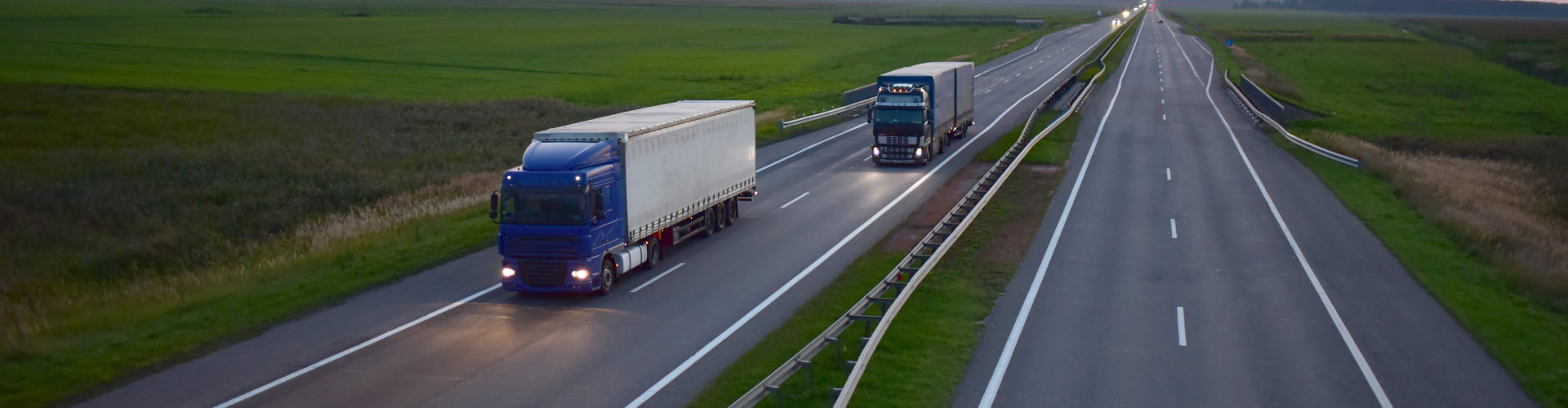 Truck with semi-trailer driving along highway on the sunset background. Goods delivery by roads. Services and Transport logistics. Soft focus, possible granularity.